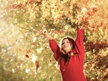 Femme détendant dans des feuilles de lancement de parc d'automne dans le ciel Photographie stock