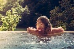 Femme détendant dans la piscine d'hôtel regardant la vue Photo libre de droits