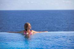 Femme détendant dans la piscine d'infini en été Photos libres de droits