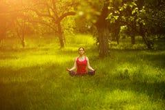 Femme détendant dans la pose Sukhasana de yoga Images stock