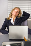 Femme détendant dans le bureau avec un ordinateur portatif photographie stock
