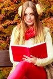 Femme détendant dans le livre automnal de lecture de parc Photos libres de droits