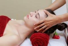 Femme détendant dans le traitement de beauté, massage facial Image libre de droits