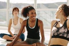 Femme détendant et parlant après session de yoga Photos libres de droits
