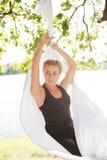 Femme détendant et pratiquant le yoga anti-gravité à l'arbre Image libre de droits
