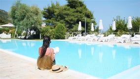 Femme détendant par la piscine dans une station de vacances d'hôtel de luxe appréciant des vacances parfaites de vacances de plag banque de vidéos