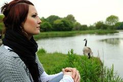 Femme détendant par le fleuve Images stock