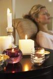 Femme détendant par le Tableau avec des bougies de Lit Photographie stock