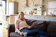 Femme détendant sur l'appartement de Sofa Reading Newspaper In Modern images stock