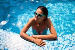 Femme détendant sur l'eau de piscine dans le jour ensoleillé chaud Résumé Photographie stock