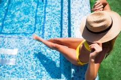 Femme détendant sur l'eau de piscine dans le jour ensoleillé chaud Résumé Images stock
