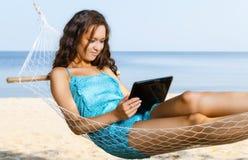 Femme détendant sur l'hamac et à l'aide du comprimé numérique Photo libre de droits