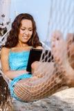 Femme détendant sur l'hamac et à l'aide du comprimé numérique Images stock