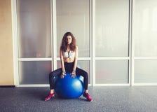 Femme détendant sur la boule dans le gymnase image libre de droits