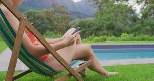 Femme détendant sur la chaise de plage dans l'arrière-cour 4k clips vidéos