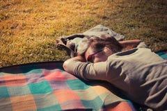Femme détendant sur la couverture au coucher du soleil Photos stock