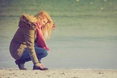 Femme détendant sur la plage, jour froid photographie stock