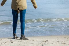 Femme détendant sur la plage, jour froid, jambes seulement Photo stock