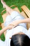 Femme détendant sur la présidence paresseuse en bambou image stock