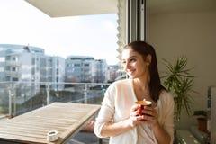 Femme détendant sur le balcon tenant la tasse de café ou de thé photographie stock