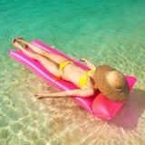 Femme détendant sur le matelas gonflable Photo stock