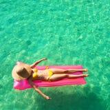 Femme détendant sur le matelas gonflable Image stock