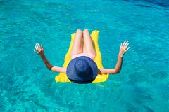 Femme détendant sur le matelas gonflable en mer Images stock