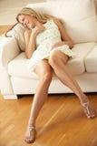 Femme détendant sur le sofa à la maison images libres de droits