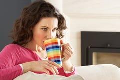 Femme détendant sur le sofa à la maison buvant du café photos libres de droits
