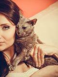 Femme détendant sur le sofa, animal familier de chat dans des ses mains Photos stock