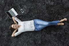 Femme détendant sur le tapis image libre de droits