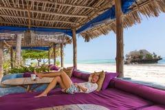 Femme détendue dans le fainéant tropical de luxe de barre, appréciant des vacances d'été sur la belle plage photo stock