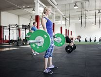 Femme déterminée d'ajustement soulevant le Barbell vert Photos stock