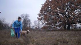Femme d'écologie avec les déchets de nettoyage de chien en nature banque de vidéos