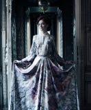 Femme d'élégance avec la robe de vol dans la chambre de palais Images libres de droits