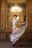 Femme d'élégance avec la robe de vol dans la chambre de palais photo stock