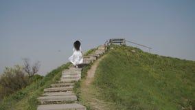 Femme d'élégance dans la longue robe blanche relevant les escaliers sur la colline verte banque de vidéos