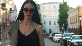Femme d'élégance dans les vêtements à la mode et des lunettes de soleil marchant dans le mouvement lent banque de vidéos