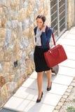 Femme d'élégance laissant le bagage à la maison appelle le téléphone Image libre de droits