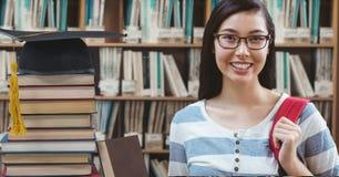 Femme d'étudiant dans la bibliothèque d'éducation avec le chapeau et les livres d'obtention du diplôme photos libres de droits