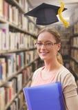 Femme d'étudiant dans la bibliothèque d'éducation avec le chapeau d'obtention du diplôme photographie stock libre de droits