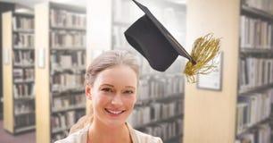 Femme d'étudiant dans la bibliothèque d'éducation avec le chapeau d'obtention du diplôme image libre de droits