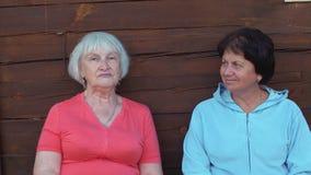Femme d'aîné du portrait deux posant et regardant in camera sur le fond en bois de mur banque de vidéos