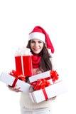 Femme d'achats de Noël retenant beaucoup de cadeaux de Noël dans des ses bras portant le chapeau de Santa et le vêtement de l'hiv photographie stock