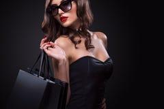 Femme d'achats jugeant le sac gris d'isolement sur le fond foncé dans des vacances noires de vendredi photos stock