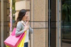 Femme d'achats regardant l'affichage de fenêtre d'habillement Photos stock