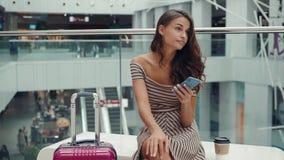 Femme d'achats souriant avec des sacs parlant au téléphone dans le mail Belle fille avec le smartphone dans des bagages de centre banque de vidéos