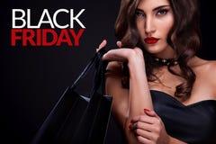 Femme d'achats tenant le sac gris sur le fond foncé dans des vacances noires de vendredi photo libre de droits