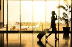 Femme d'affaires à l'aéroport - silhouette d'un passager Image libre de droits