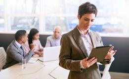 Femme d'affaires à l'aide d'un comprimé tout en se tenant devant des collègues Image libre de droits